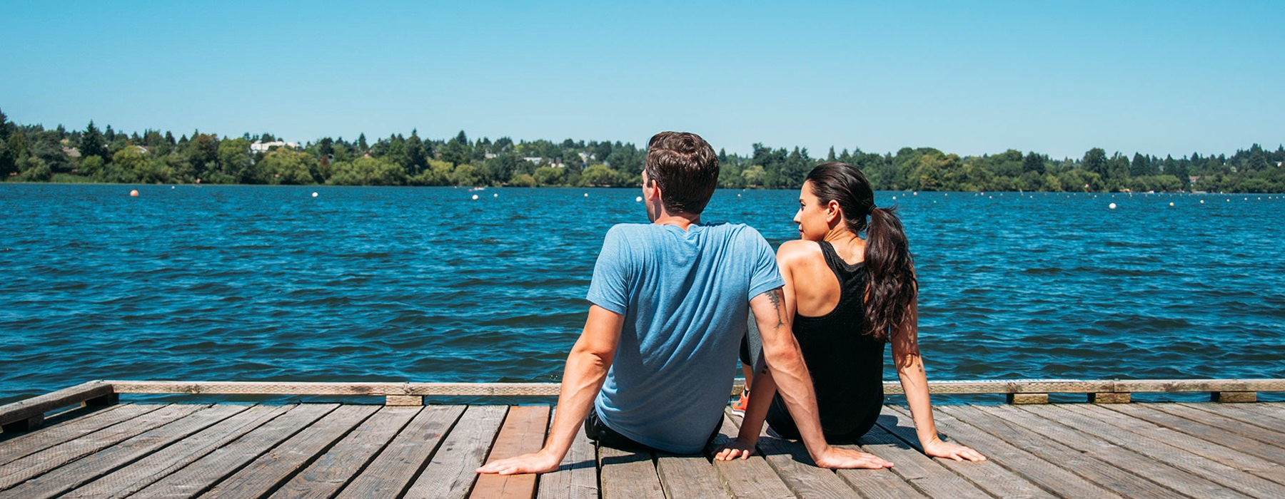 couple sitting on the dock looking at the lake